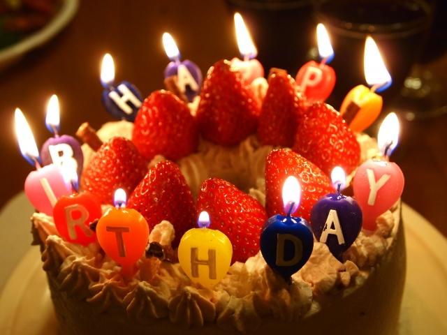 ろうそくが灯る誕生日ケーキ
